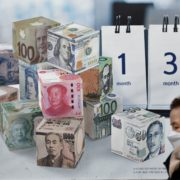 corona-finance_A woman wearing a face mask walks past a currency exchange sign